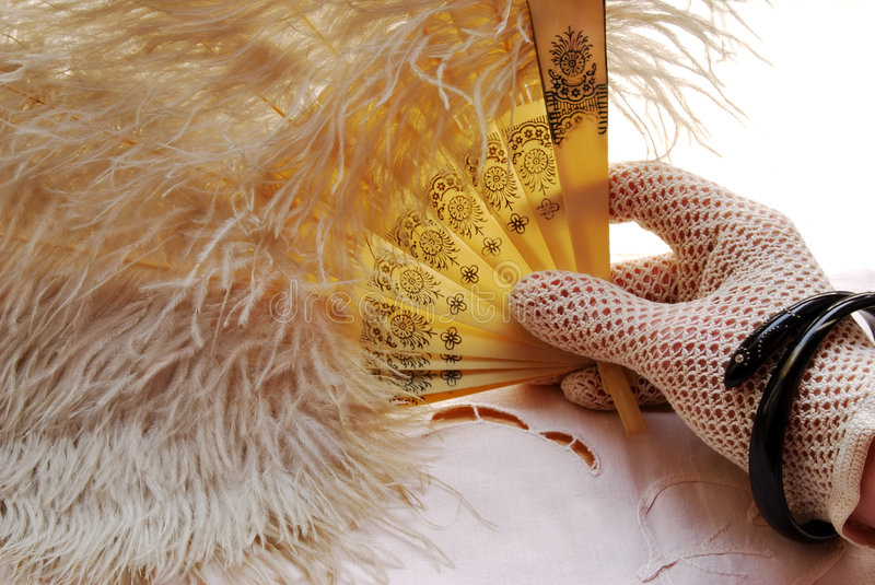 Hand with old fan. Woman´s hand in crocheted glove holding old feather fan royalty free stock photos