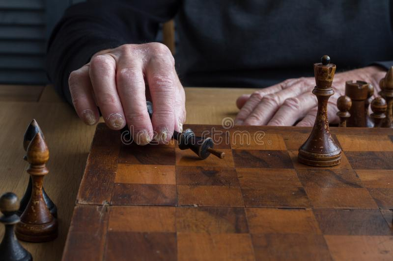 The hand of an old man puts a black kings figure on the board acknowledging loss, concept business games, selective focus. Copyspace royalty free stock photo
