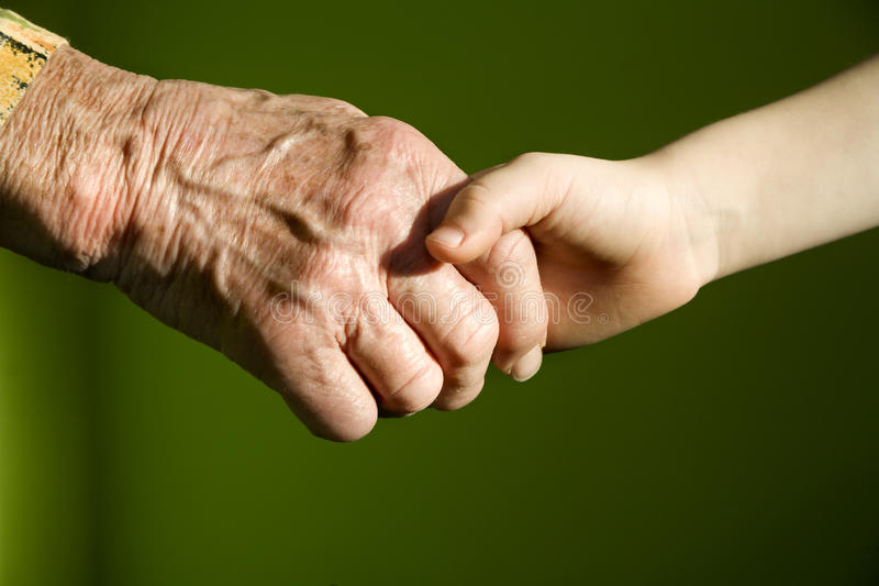 Hand of old woman and child royalty free stock photography