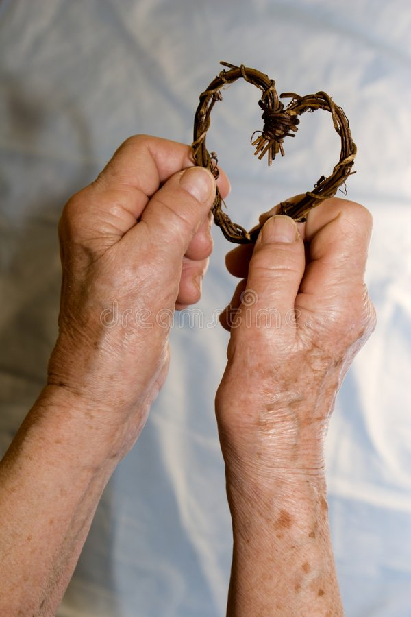 Hand of old woman and heart. Hand of old woman and decoration heart royalty free stock images