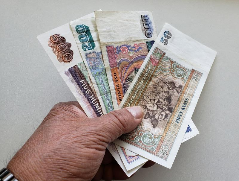 hand of an older man holding burmese banknotes royalty free stock photo