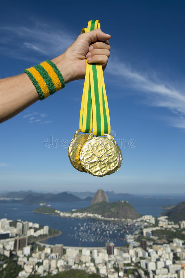 Hand of Olympic Athlete Holding Gold Medals Rio Skyline. Hand of first place Olympic athlete with Brazil colors wristband holding gold medals at Rio de Janeiro stock photo