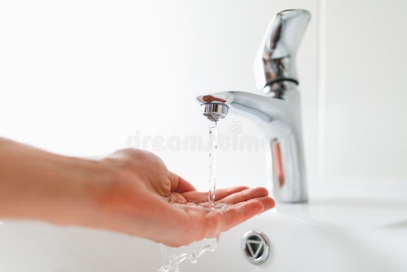 Hand onder tapkraan met waterstroom stock foto's