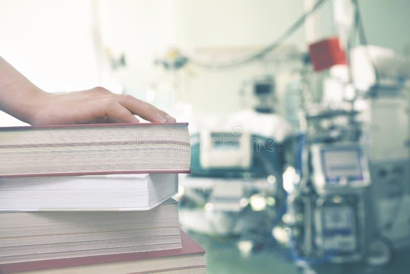 Hand op de boeken tegen de achtergrond van medische apparatuur royalty-vrije stock foto