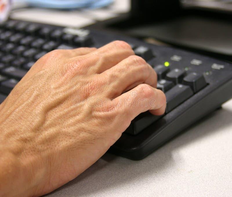 Hand op toetsenbord royalty-vrije stock afbeelding