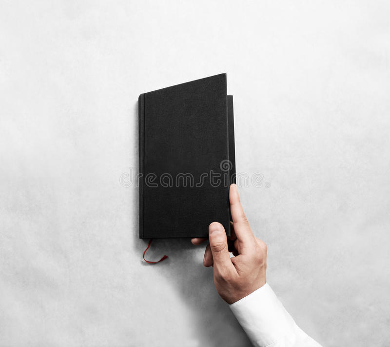 Hand open blank black book cover mock up template. stock photos