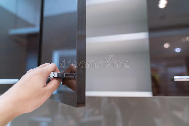 Hand Open Kitchen Cabinet. Close up hand Open Kitchen Cabinet royalty free stock photo