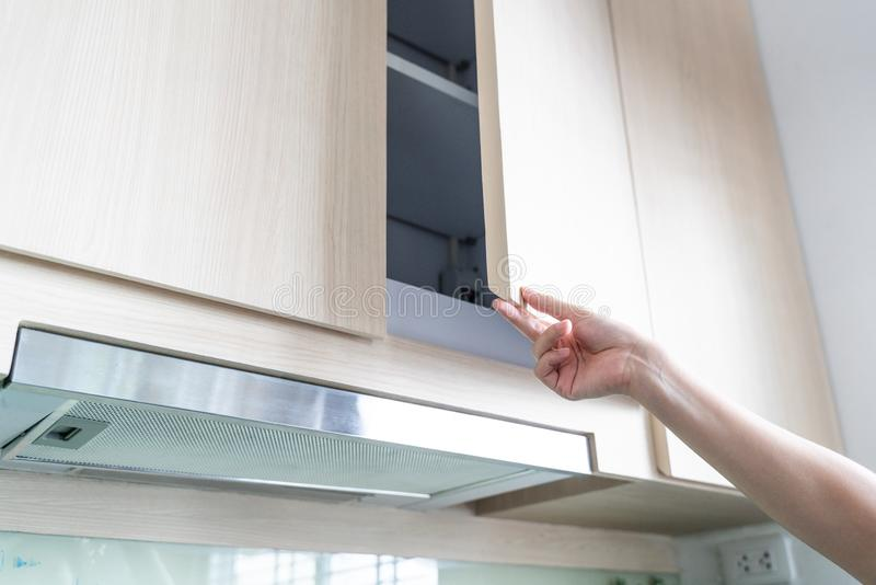 Hand Open Kitchen Cabinet. Close up of hand Open Kitchen Cabinet royalty free stock photo