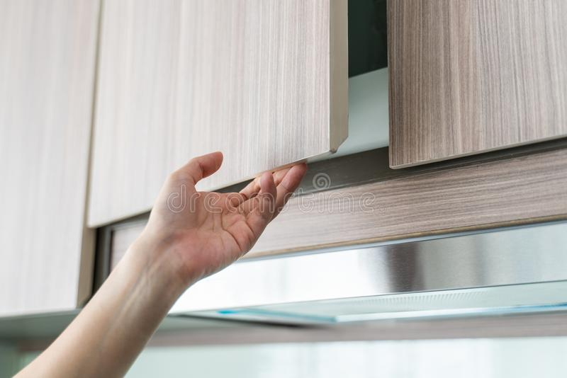 Hand Open Kitchen Cabinet. Close up of hand Open Kitchen Cabinet royalty free stock photos