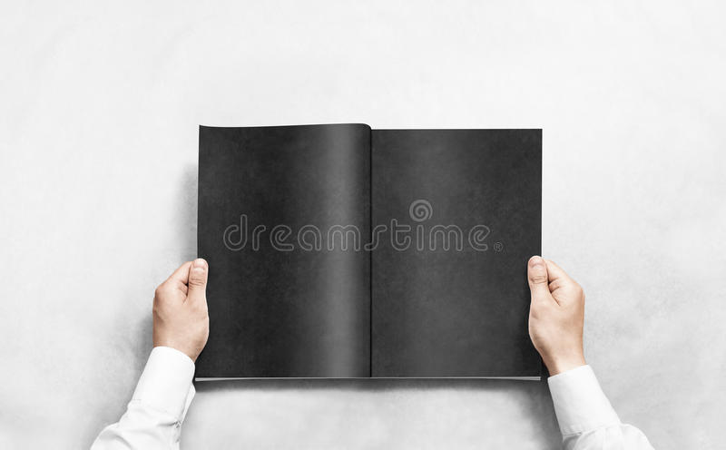 Hand opening black journal with blank pages mockup. Arm in shirt holding grey magazine template mock up. Man reading double-pages book first person view. Mag stock images