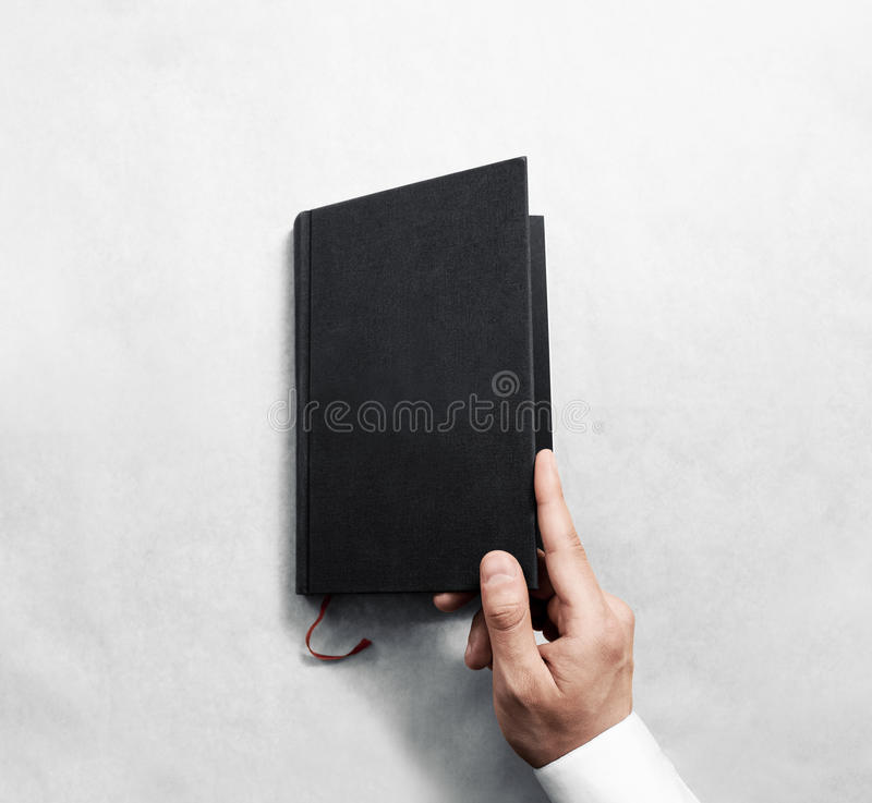 Hand opening blank black book cover mockup template. Clear booklet front surface design mock up. Arm holding opened textbook diary. Reading grey notebook copy royalty free stock photos