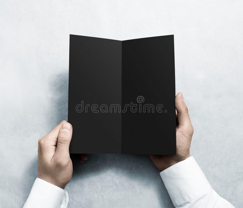 Hand opening blank black flyer brochure booklet mockup. Leaflet presentation. Pamphlet mock up holding hand. Man show grey offset paper. Booklet design stock photography