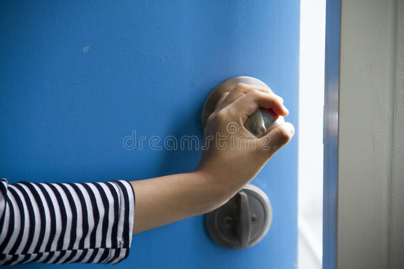 The hand is opening the blue door to go out. stock images