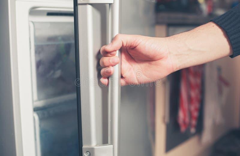 Hand opening freezer door. The hand of a young man is opening a freezer door stock photos