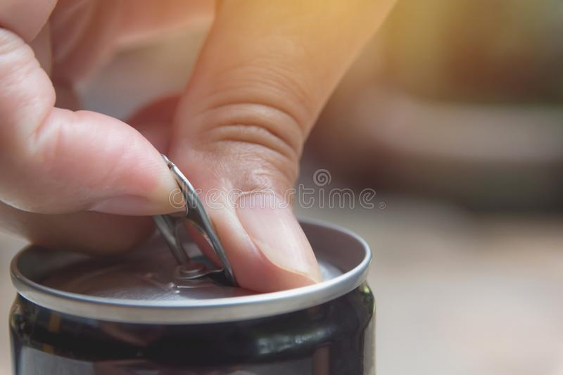 Hand opening an iron can. Can with a drink of cola stock images