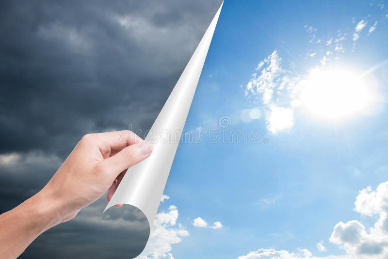 Hand opening page overcast to bright blue sky. royalty free stock photo