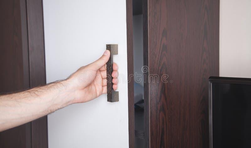 Hand opening wardrobe doors in home stock images