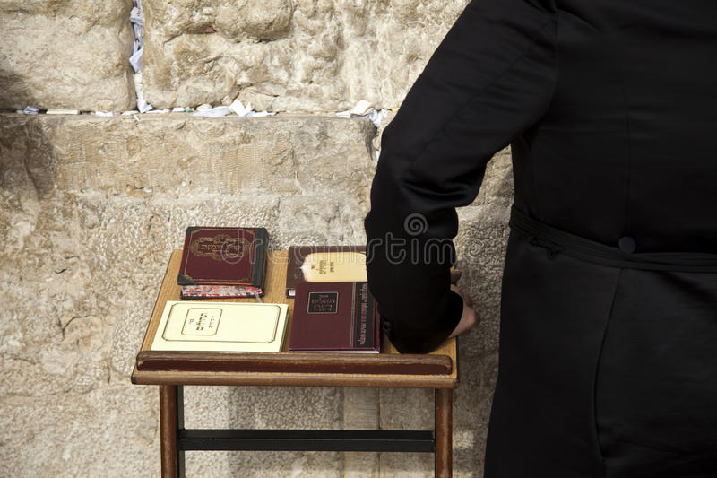 Psalms Books at the Wailing Wall. The hand of an orthodox Jewish man resting on a pedistal with four editions of the biblical book of psalms. Shot at the wailing stock photo