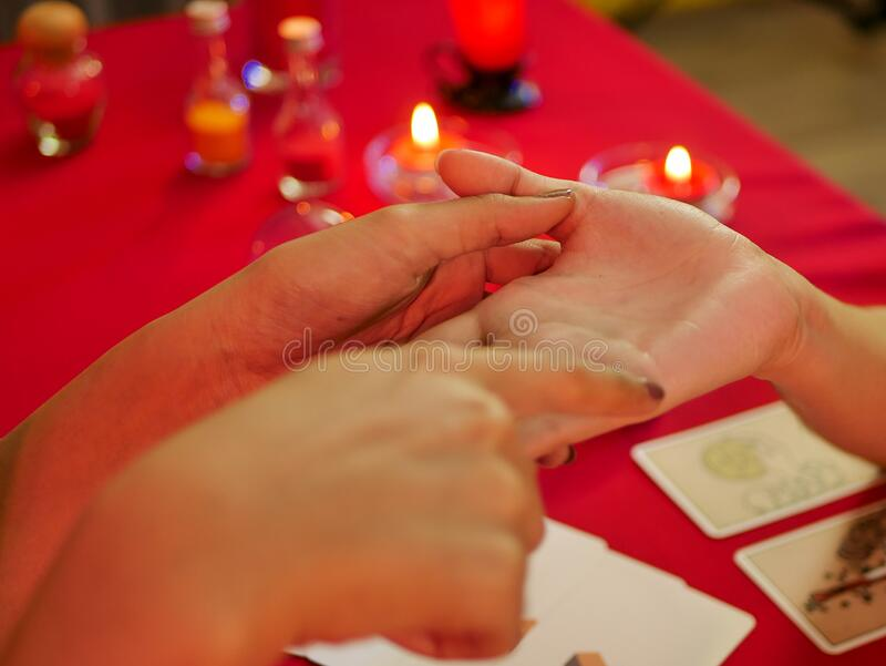 Hand out the customer at the fortune teller palm reading using Divine magic to forecast the future royalty free stock image