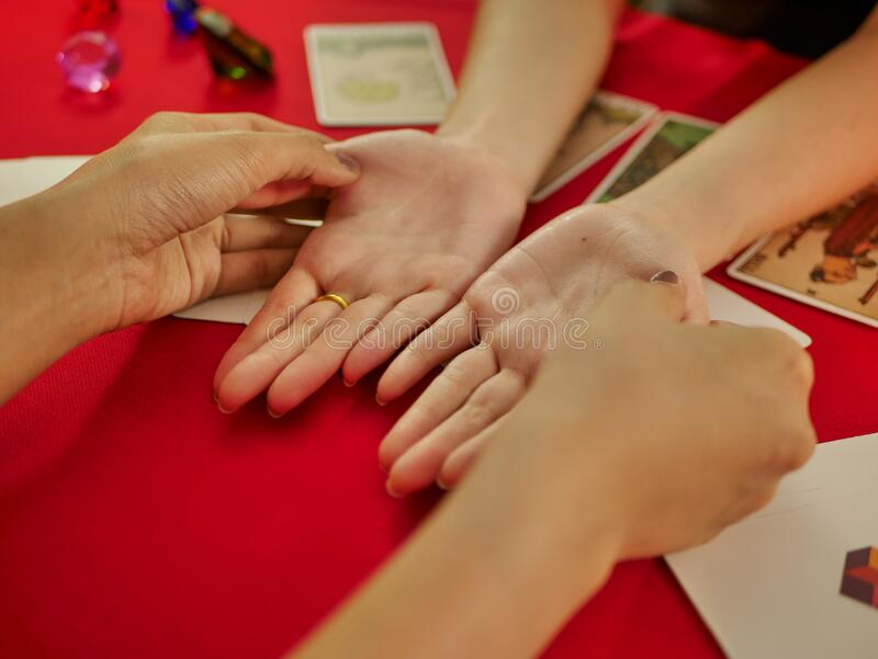 Hand out the customer at the fortune teller palm reading using Divine magic to forecast the future stock images
