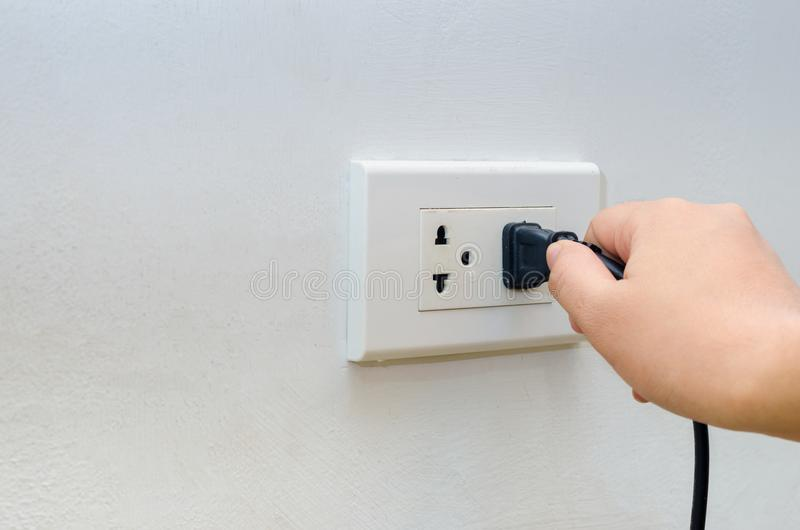Hand outlet Power saving Hand inserting electrical plug into outlet royalty free stock images