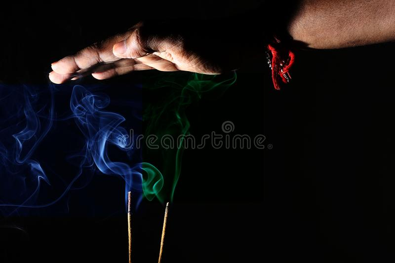 Hand over coloreó el humo que salía de los palillos del incienso Abstraiga el arte del humo imagen de archivo libre de regalías