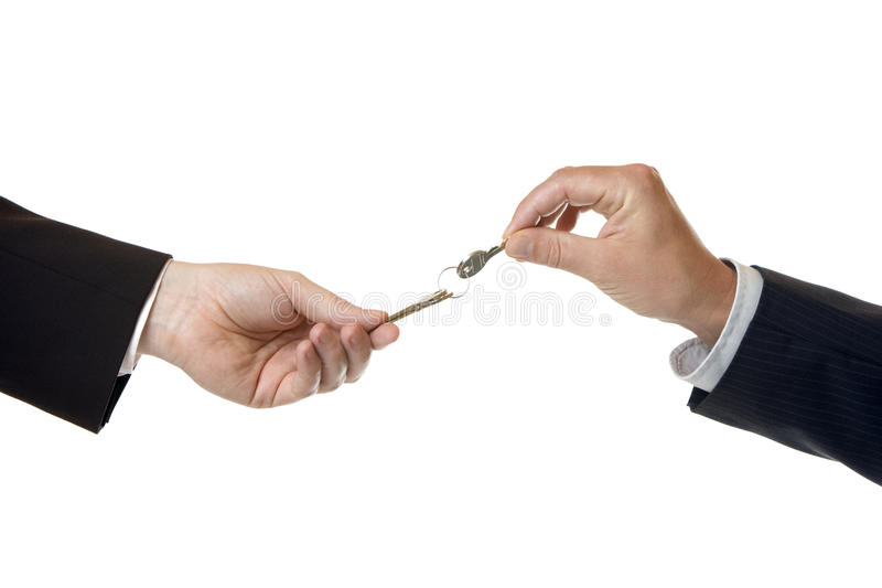 Hand over of key to success. One businessman gives another businessman a key stock image
