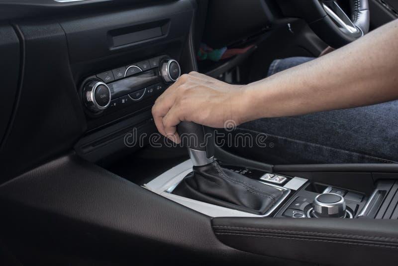 Hand p? det skiftande kugghjulet p? bilen, man som k?r bilen royaltyfri foto