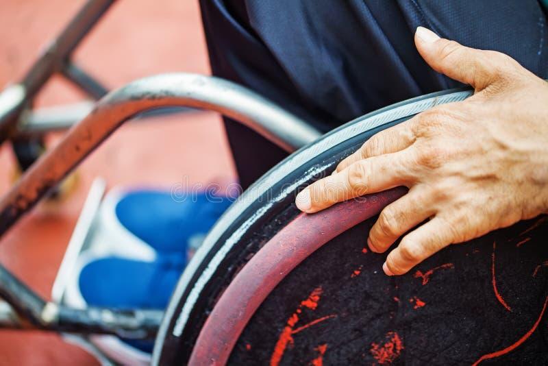 Hand på ett hjul av rullstolen arkivfoton