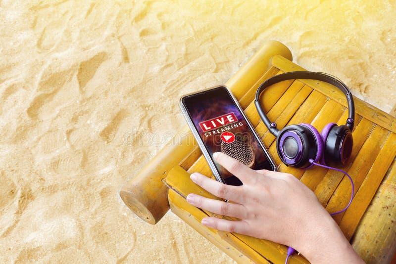 Hand på mobiltelefonen med levande musiktryckning och hörlurar fotografering för bildbyråer