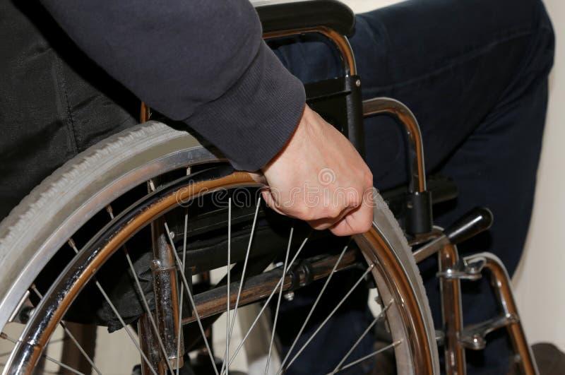 Hand på rullstolen i sovrummet av handikappade personermannen royaltyfri fotografi