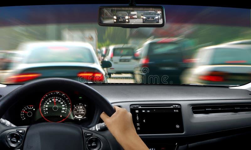 Hand på styrninghjulet under trafikstockning arkivbild