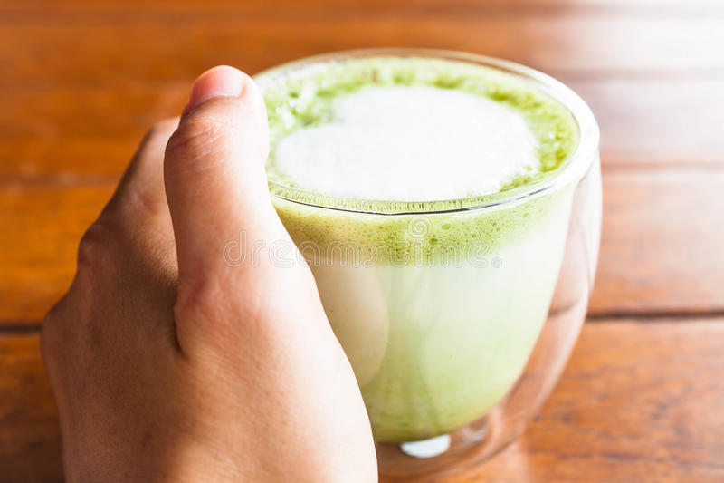 Hand på varm latte för grönt te för matcha arkivfoto
