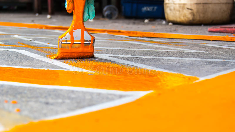 Hand with paint brush, painting road No parking yellow line area royalty free stock photos