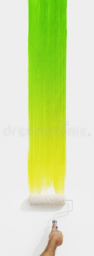 Hand with paint roller painting color green, close up isolated stock photos