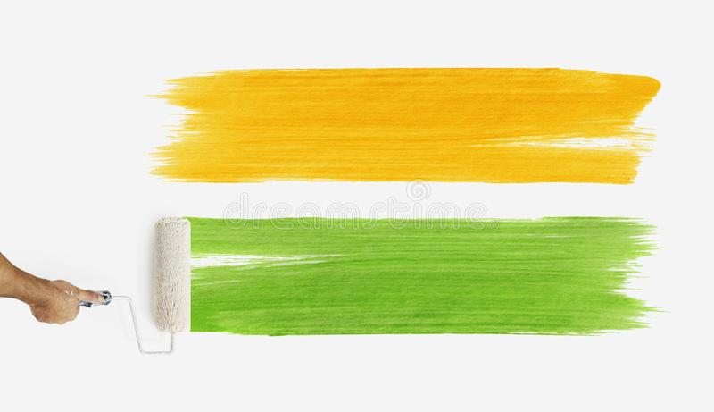 Hand with paint roller painting color orange and green, close up royalty free stock photos