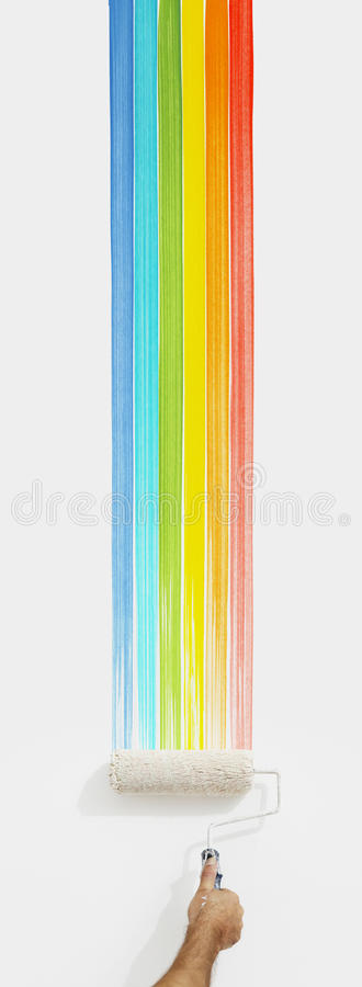 Hand with paint roller painting color rainbow, close up isolated stock images