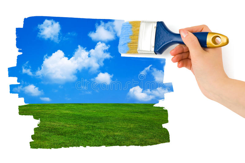 Hand with paintbrush drawing landscape royalty free stock photography
