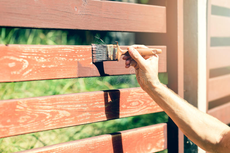 Hand with paintbrush painting wooden fence royalty free stock photo