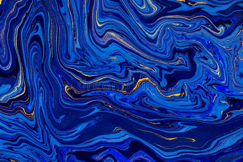 Hand painted background with mixed liquid blue and golden paints. Abstract fluid acrylic painting. Modern art. Marbled. Blue abstract background. Liquid marble royalty free stock images