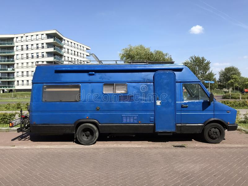 Hand painted Blue 1980`s Fiat camper van. Almere, the Netherlands - August 22, 2019: Hand painted Blue 1980`s Fiat camper van parked by the side of the road stock images