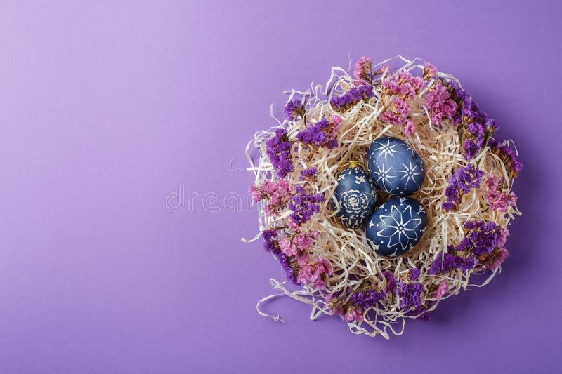 Hand painted dark blue easter eggs in nest and flowers on violet stock images