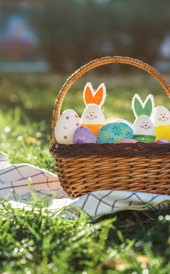 Hand painted Easter eggs and bunny in big rattan basket on green grass on white towel. Traditional decoration for Easter stock photography