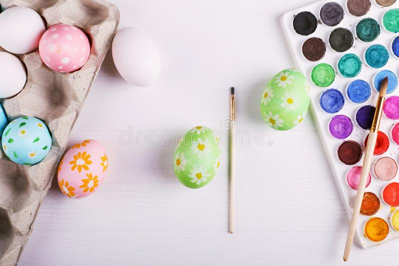 Hand painted Easter eggs, paints and brushes on a white table. Preparation for the holiday royalty free stock image