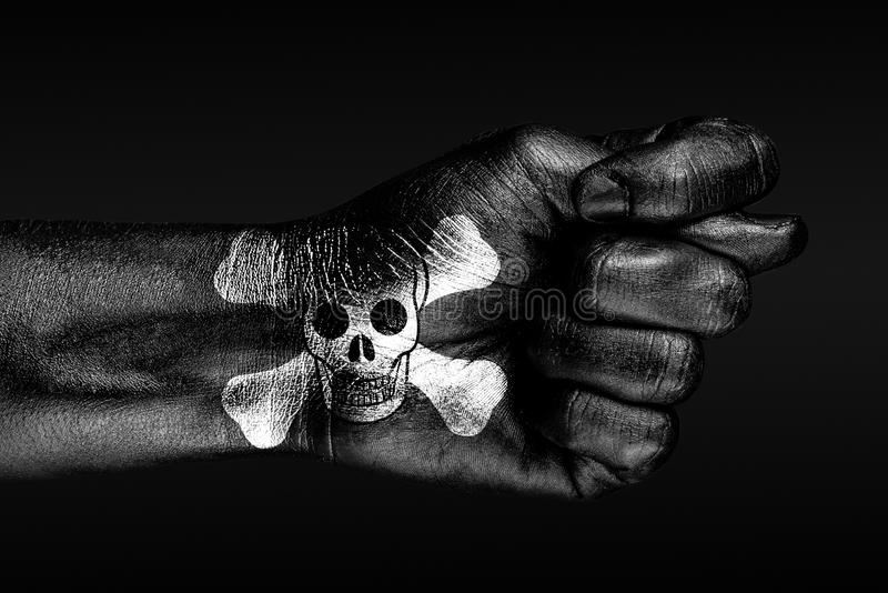 On a hand with a painted human skull and bones depicted a fig, a sign of aggression, disagreement, piracy, on a dark background. Horizontal frame royalty free stock photography