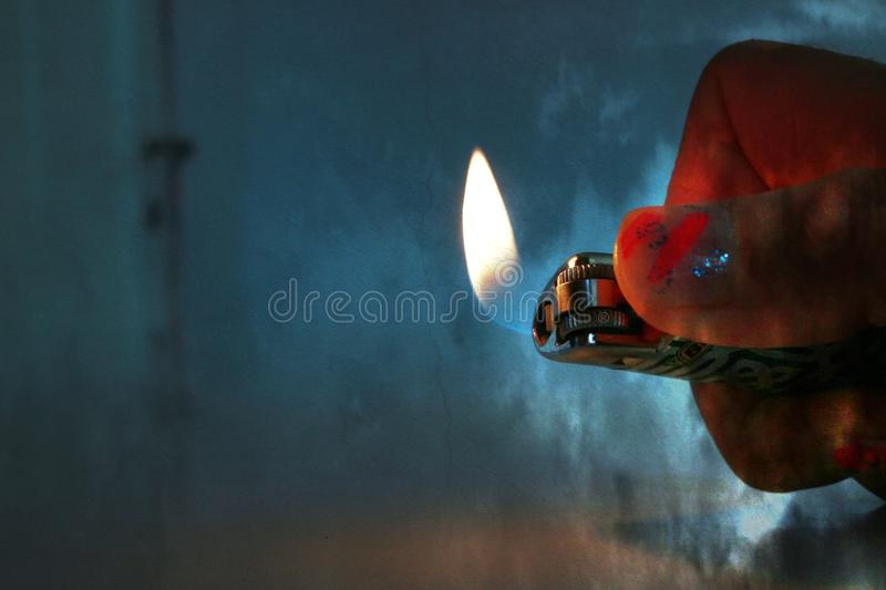 A woman's hand with painted nails is holding a lit lighter in a dark room royalty free stock photo