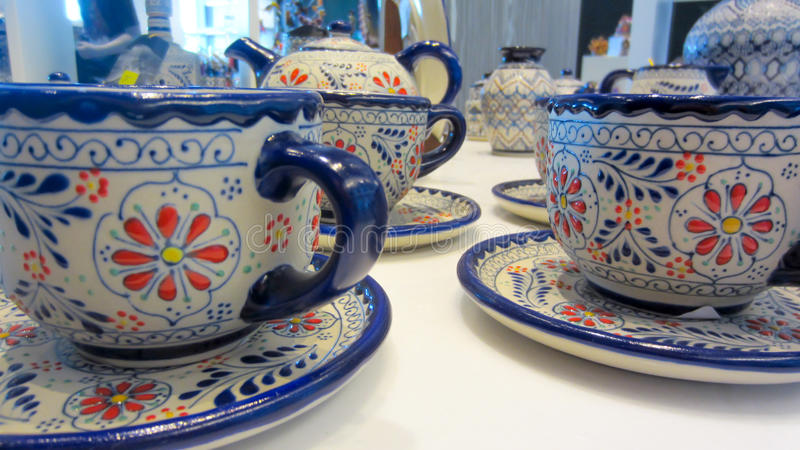 Hand-painted pottery in Mexico shop. Beautiful, hand-painted patterns on delicate pottery with bright blue trim at a Mexican shop stock images