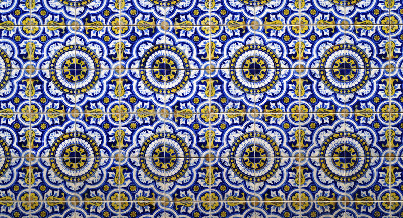 Hand painted tiles texture background. A pattern made of tiles painted by hand with some flower in the corners and some details in yellow and blue royalty free stock photography