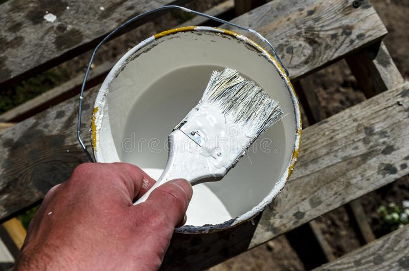 Hand painter with a brush and a jar of white paint is preparing to paint the house, wall stock photography