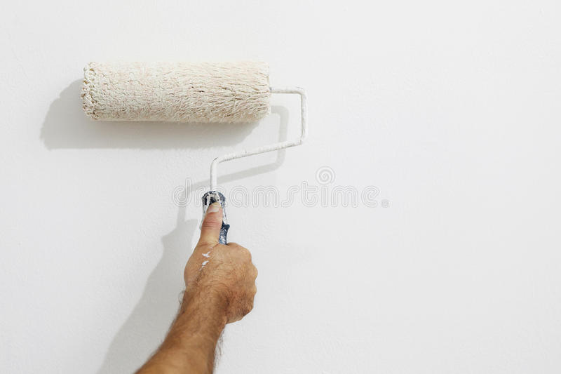 Hand painter man at work with a paint roller, wall painting royalty free stock photography